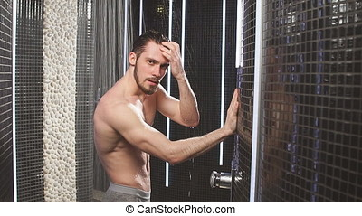 Young sportsman is taking a shower after jogging. Touch...