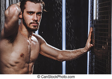 young sportsman is taking a shower after jogging