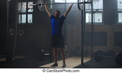 Young sportsman lifting heavy barbell. Healthy, muscular. Strong man doing barbell snatch exercise at the gym in slow motion. Sportsman on exercise mat doing situps in gym. Muscular athlete doing abs workout.