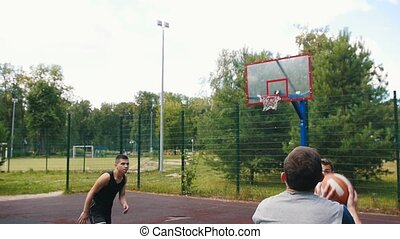 Young sportsman playing basketball on the court outdoors with friends, dribbling and missing the basket