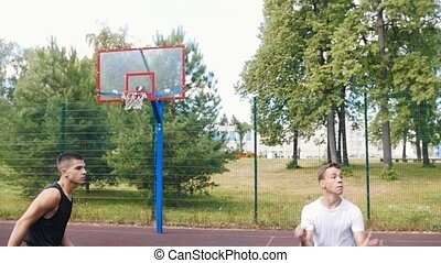 Young sportsman playing basketball on the court outdoors with friends, throwing the ball and missing the basket