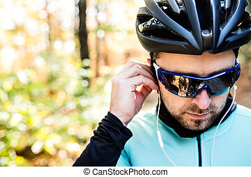 Young sportsman riding bicycle outside in sunny autumn...