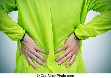 young sportsman with low back pain - a young caucasian...