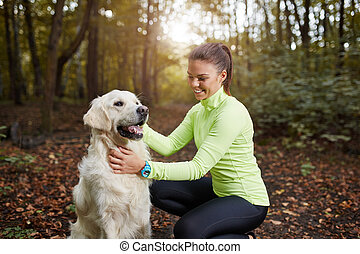 Young sportswoman and her dog - Portrait of young beautiful ...