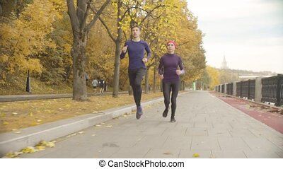 Young sportswoman and sportsman running along the road -...