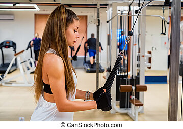 Young sportswoman does lat pull down exercise in gym - Side...