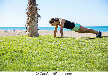 Young sportswoman doing push-ups on beach - Side portrait of...