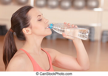 Young sportswoman drinking water after training