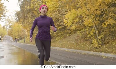 Young sportswoman running along the road - Slow motion of...