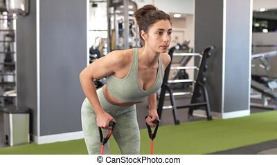 Young sportswoman warming up with fitness gums in the gym wearing sportswear