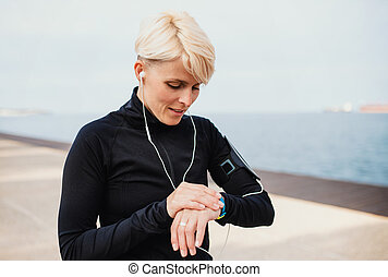 Young sportswoman with earphones standing outdoors on beach, using smartwatch.