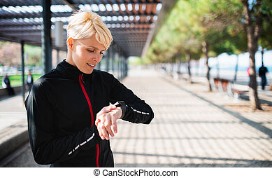 Young sportswoman with smartwatch resting after doing exercise outdoors.
