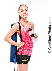 Young sportswoman with yoga mat and bottle of water
