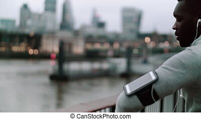 Young sporty black man runner standing on the bridge in a city, using smartwatch.
