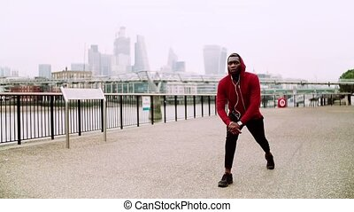 Young sporty black man runner stretching on the bridge outside in a London city.