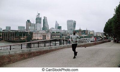 Young sporty black man runner with smart phone running on the bridge in a city.