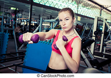 Young sporty blond woman do physical exercises with weight in gym