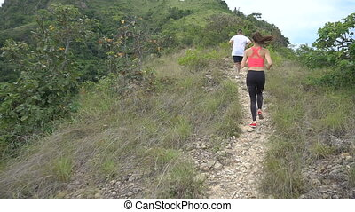 Young sporty boy and girl jogging on mountain track. Woman and man work out in nature. Slow motion