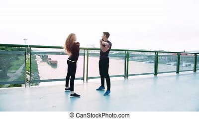 Young sporty couple standing on the bridge in the city,...