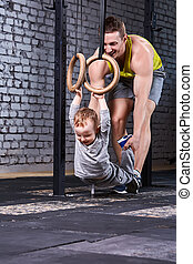 Young sporty father trains the little son with gymnastic rings against brick wall at the cross fit gym.