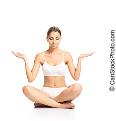 Young, sporty, fit and beautiful girl meditating isolated on white