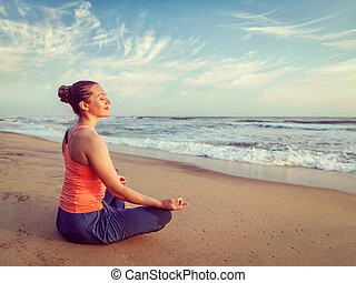 Young sporty fit woman doing yoga oudoors at beach - Vintage...