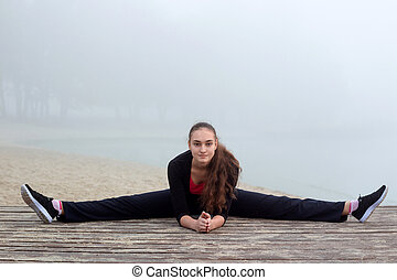 Young sporty girl does stretching exercises during fitness workout outdoor