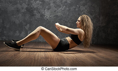 Young sporty girl performing sit up exercises fitness training