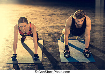 Young sporty man and woman doing plank exercise with dumbbells