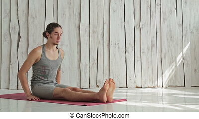 young sporty woman practicing yoga in fitness studio