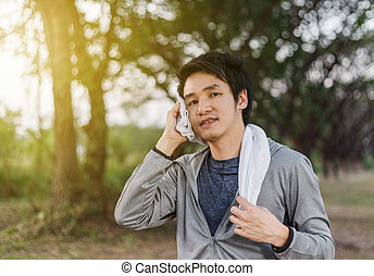 young sporty man resting and wiping his sweat with a towel after workout sport exercises outdoors at park