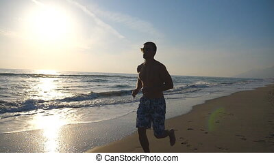 Young sporty man running on the sea beach during sunrise. Athletic boy jogging along ocean coast. Male sportsman exercising outdoor. Healthy active lifestyle. Close up Slow motion