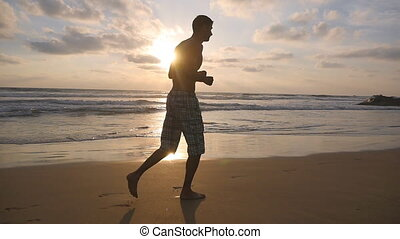 Young sporty man running on the sea beach at sunset. Athletic guy jogging along ocean shore during sunrise. Male sportsman exercising outdoor. Healthy active lifestyle. Workout at nature. Slow motion