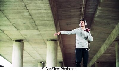 Young sporty man with headphones in the city, listening to music and dancing.