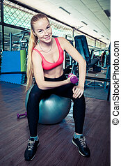 Young sporty woman do physical exercises with weight on fit-ball in gym