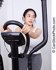 sporty woman doing exercises with elliptical trainer - young...
