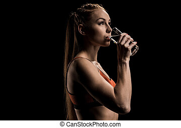 young sporty woman drinking water from glass and looking away