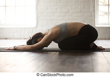 Young sporty woman in Balasana pose, white loft studio backgroun