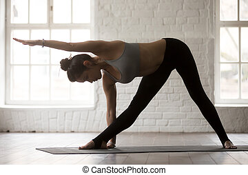 Young sporty woman in Utthita Trikonasana pose, white loft studi