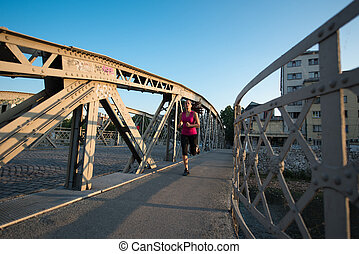 woman jogging across the bridge at sunny morning