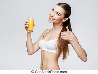 sporty woman over gray background holding glass of orange juice