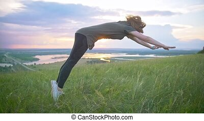 Young sporty woman performing a flip on the grass at summer sunset