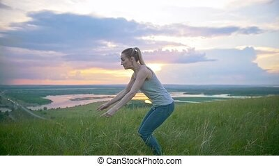 Young sporty woman performing an acrobatic jump on the hill at summer sunset