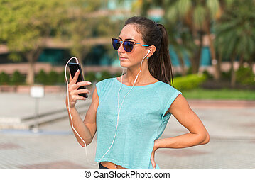 Young sporty woman resting after exercising using her smartphone and listening to music in earphones. Athlete runner in sportswear taking a break
