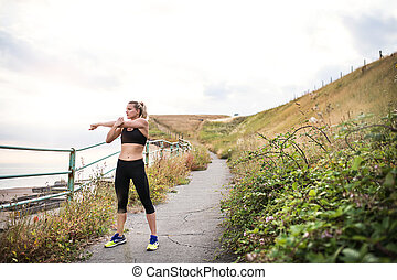 Young sporty woman runner in black activewear standing outside in nature, stretching.