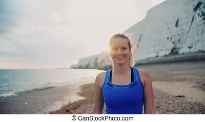Young sporty woman runner in blue sportswear walking on the...