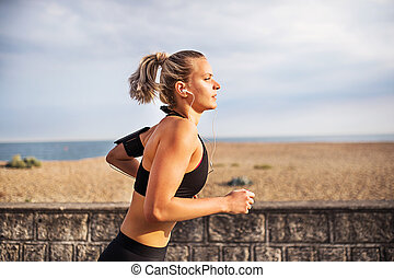 Young sporty woman runner running outside on a beach in nature.