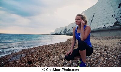 Young sporty woman runner with earphones in blue sportswear...