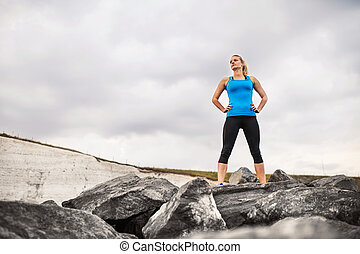Young sporty woman runner with earphones standing on the rocks outside.