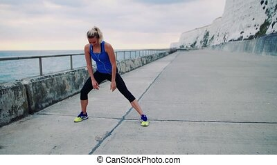 Young sporty woman runner with earphones stretching on the...